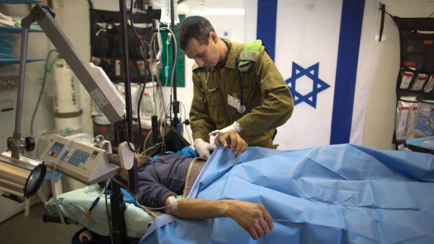 Israeli military medic tends  a Syrian man who was wounded in the ongoing violence in Syria, in a military hospital located in the Golan Heights near the border with Syria on Tuesday, Feb. 18, 2014. Since the Syrian conflict erupted almost three years ago hundreds of Syrians have received treatment in Israeli hospitals.(AP Photo/Menahem Kahana, Pool)