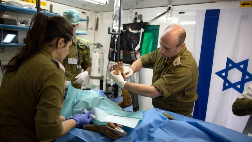 Members of the Israeli army medical staff tend to a Syrian man who was wounded in the ongoing violence in Syria, in a military hospital located in the Golan Heights near the border with Syria on Tuesday, Feb. 18, 2014. Since the Syrian conflict erupted almost three years ago hundreds of Syrians have received treatment in Israeli hospitals.(AP Photo/Menahem Kahana, Pool)