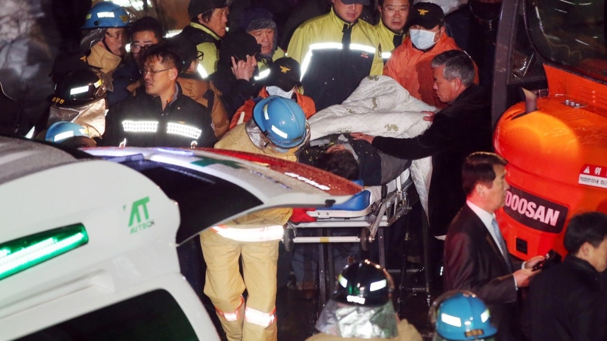 Rescue workers carry a stretcher with a victim from a collapsed resort building in Gyeongju, South Korea, Tuesday, Feb. 18, 2014. The roof of a resort's auditorium collapsed during a welcoming ceremony for South Korean university freshmen, killing nine and likely trapping about 10, officials said Tuesday. (AP Photo/Yonhap, Lee Jae-hyuck)  Korea Out