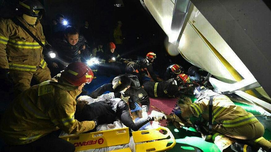 Rescue workers prepare to carry a victim, center front, as other rescuers try to find out more victims from a collapsed resort building in Gyeongju, South Korea, Tuesday, Feb. 18, 2014. The roof of a resort auditorium collapsed during a welcoming ceremony for South Korean university freshmen, killing nine and likely trapping about 10, officials said Tuesday. (AP Photo/Yonhap, Lee Jae-hyuck)  KOREA OUT