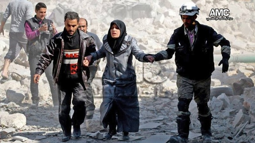 Feb. 17, 2014: This photo provided by the anti-government activist group Aleppo Media Center (AMC), which has been authenticated based on its contents and other AP reporting, shows Syrian men helping a survivor out of a destroyed building after a Syrian forces warplanes attacked Masaken Hanano neighborhood, in Aleppo, Syria.