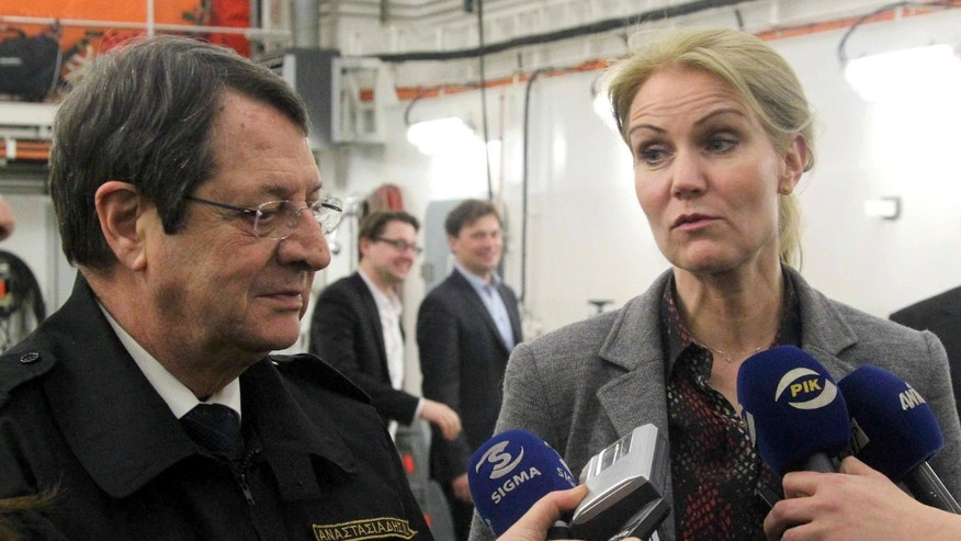 Cyprus President Nicos Anastasiades looks the Prime Minister of Denmark, Helle Thorning Schmidt as she speaks to the media aboard the Danish frigate HDMS Esbern Snare at the Cypriot port of Larnaca on Wednesday, Feb. 19, 2014. Thorning-Schmidt visited the frigate which is part of a joint Danish-Norwegian operation tasked with ferrying Syria's chemical weapons out of the strife-torn country. (AP Photo/Press and Information Office)