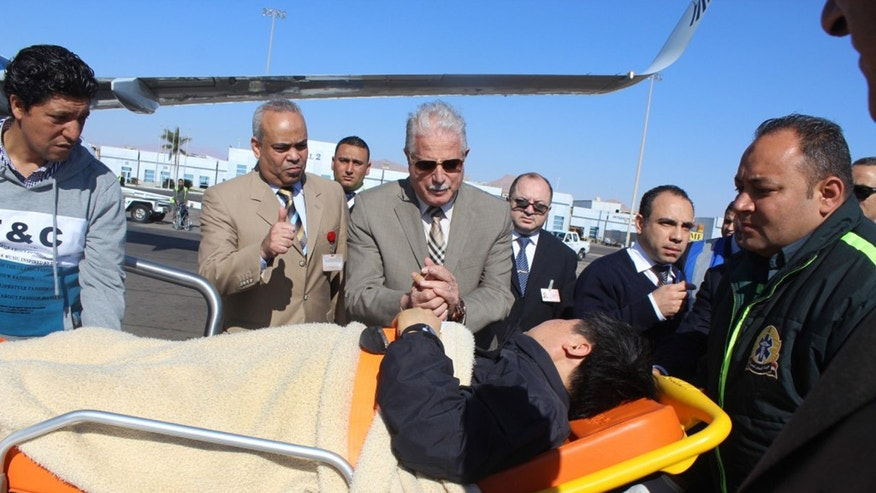 In this photo released by the Office of the South Sinai Governor, Governor of South Sinai, Major General Khaled Foda, center, and other officials sees off a South Korean tourist who was wounded in a deadly blast Sunday, on a bus in Taba, being evacuated home, at Sharm el Sheikh airport, Egypt, Wednesday, Feb. 19, 2014. The bombing Sunday was the first targeting foreign tourists in the Sinai in nearly decade, raising fears that Islamic militants who have been waging a campaign of violence against security forces in the peninsula are now turning to attack tourism, a pillar of Egypt's economy. (AP Photo/Office of the South Sinai Governor)