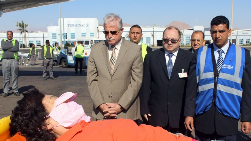 In this photo released by the Office of the South Sinai Governor, the governor of South Sinai, Major General Khaled Foda, center left, and other officials, watch as a South Korean tourist who was wounded in a deadly blast Sunday, on a bus in Taba, is evacuated to her home country, at Sharm el Sheikh airport, Egypt, Wednesday, Feb. 19, 2014. The bombing Sunday was the first targeting foreign tourists in the Sinai in nearly decade, raising fears that Islamic militants who have been waging a campaign of violence against security forces in the peninsula are now turning to attack tourism, a pillar of Egypt's economy. (AP Photo/Office of the South Sinai Governor)