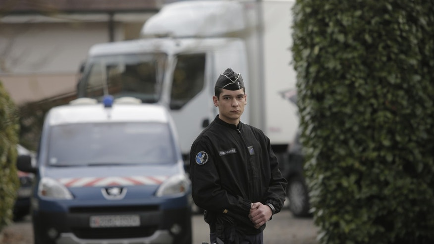 A French gendarme blocks the access to a house in a residential area in Talloires, French Alps,  Tuesday, Feb. 18, 2014, as part of the continuing investigation into the grisly shooting deaths of a British-Iraqi man and three others nearly 18-months ago.  French police announced Tuesday they have detained a 48-year old man, a resident of eastern France, in connection with the deaths. (AP Photo/Laurent Cipriani)