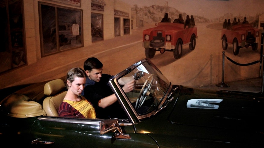 In this Monday, Feb. 10, 2014 photo, Students from Denmark Thomas Meulengracht Ledet, right, and Maya Berg, sit in a Mercedes car at the Royal Automobile Museum, in Amman, Jordan. On a hilltop of the Jordanian capital, the museum with some of the world's most unique cars and motorbikes recounts a century of the ruling Hashemite dynasty's elegant lifestyle. The museum was built in 2003 under instructions from King Abdullah II, specifically to pay tribute to the eventful life of his late father, Hussein, who died of cancer in 1999 after a 46-year reign. (AP Photo/Mohammad Hannon)