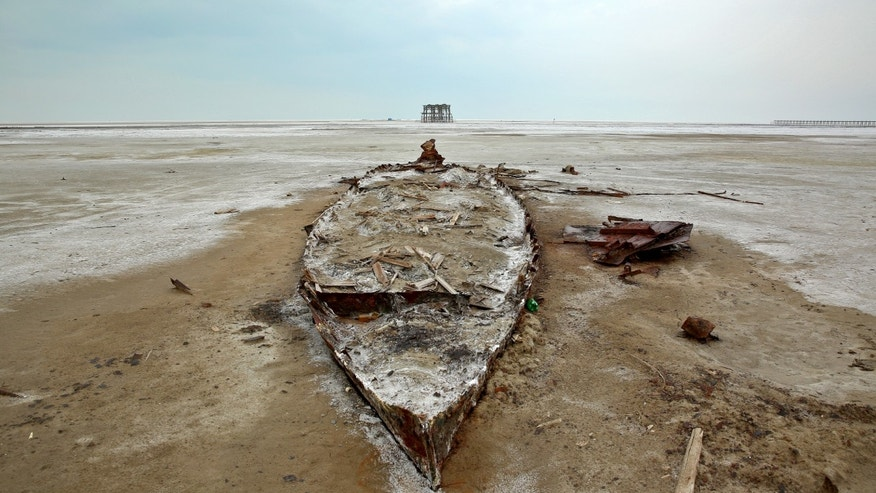 In this Sunday, Feb. 16, 2014 photo, the wreckage of a boat is stuck in the solidified salts and sands at Lake Oroumieh, northwestern Iran. Oroumieh, one of the biggest saltwater lakes on Earth, has shrunk more than 80 percent to 1,000 square kilometers (nearly 400 square miles) in the past decade. Experts fear the lake - famous in years past as a tourist spot and a favorite stopping point for migrating flamingos, pelicans and gulls - could disappear within two years if nothing is done.  (AP Photo/Ebrahim Noroozi)