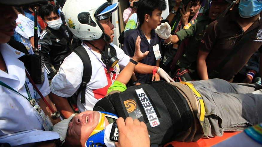 An injured foreign reporter is carried by medic team to an ambulance during a clash between police force and anti-government protesters Tuesday, Feb. 18, 2014 in Bangkok, Thailand. Clashes between police and anti-government demonstrators in Bangkok left three people dead and 57 others injured Tuesday as riot police attempted to clear out protest camps around the Thai capital. (AP Photo/Wason Wanichakorn)