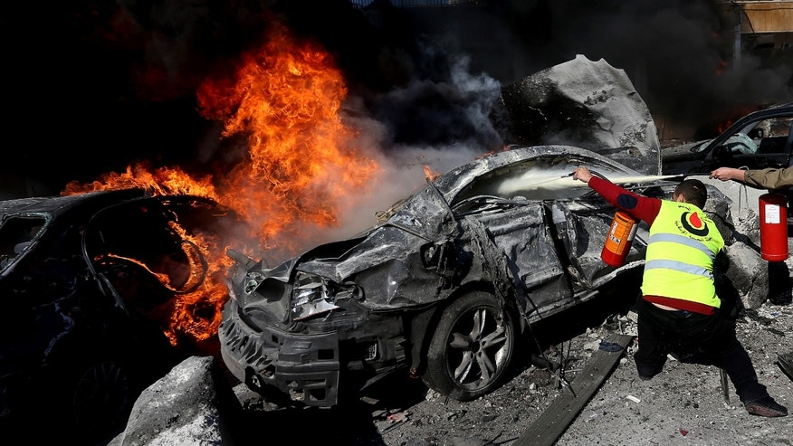 A Hezbollah civil defense worker extinguishes a burned car at the site of an explosion, near the Kuwaiti Embassy and Iran's cultural center, in the suburb of Beir Hassan, Beirut, Lebanon, Wednesday, Feb. 19, 2014. A blast in a Shiite district in southern Beirut killed at least two people on Wednesday, security officials said — the latest apparent attack linked to the civil war in neighboring Syria. (AP Photo/Hussein Malla)