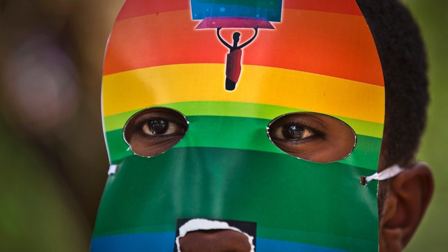 "FILE - In this Monday, Feb. 10, 2014 file photo, a Kenyan gay wears a mask to preserve his anonymity as they stage a rare protest, against Uganda's increasingly tough stance against homosexuality and in solidarity with their counterparts there, outside the Uganda High Commission in Nairobi, Kenya Monday, Feb. 10, 2014. Ugandan President Yoweri Museveni met in his office with a team of U.S.-based rights activists concerned about legislation that would impose life sentences for some homosexual acts and made clear he had no plans to sign the bill, according to Santiago Canton of the Robert F. Kennedy Center for Justice and Human Rights who attended the Jan. 18, 2014 meeting, but one month later Museveni appears to have changed his mind, saying through a spokesman in February 2014 that he would sign the bill ""to protect Ugandans from social deviants."" (AP Photo/Ben Curtis, File)"