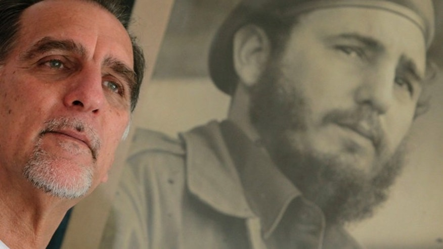 "In this Feb. 17, 2014 photo, Rene Gonzalez, the Cuban Five,"" poses for a portrait under a framed picture of Fidel Castro in Havana, Cuba.  Gonzalez was an unknown young pilot in 1990 when he pretended to steal a crop duster in Cuba and flew to Florida, using cover as a Cuban defector to spy on targets in the United States. The Cuba Five refers to intelligence agents in the employ of Fidel Castro's Cuba, they were arrested in the United States in 1998 and given terms ranging from 15 years to consecutive life sentences on charges including conspiracy and failure to register as foreign agents.  (AP Photo/Franklin Reyes)"