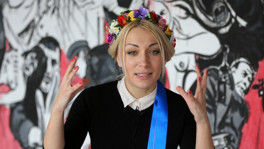 Ukrainian feminist group Femen leader Inna Shevchenko, answers questions from reporters during an interview with the Associated Press in a Paris suburb, Tuesday, Feb. 18, 2014. Nine activists from the topless women's protest movement Femen will face court in February over charges that they damaged Notre Dame cathedral during a demonstration last year. (AP Photo/Remy de la Mauviniere)