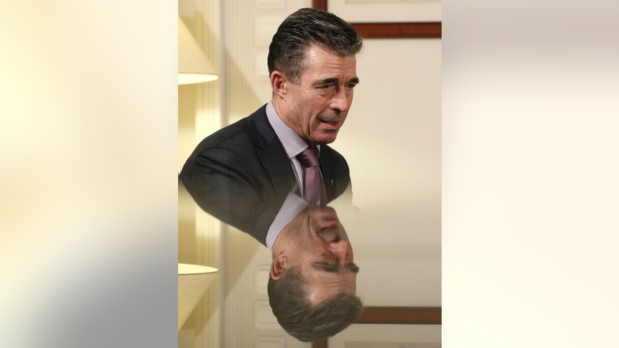 NATO Secretary General Anders Fogh Rasmussen is reflected on a glass surface as he answers question to the Associated Press, in Athens, on Thursday, Feb. 20, 2014. NATO's secretary general has expressed outrage at the extreme violence in Ukraine, where dozens of protesters have been killed in clashes with police in the country's capital, and warned the continued mayhem could affect Ukraine's relations with the alliance.(AP Photo/Petros Giannakouris)