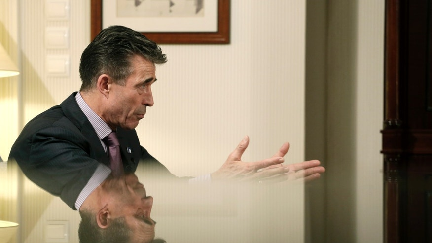 NATO Secretary General Anders Fogh Rasmussen is reflected on a glass surface as he answers a question to the Associated Press, in Athens, on Thursday, Feb. 20, 2014. NATO's secretary general has expressed outrage at the extreme violence in Ukraine, where dozens of protesters have been killed in clashes with police in the country's capital, and warned the continued mayhem could affect Ukraine's relations with the alliance. (AP Photo / Petros Giannakouris)