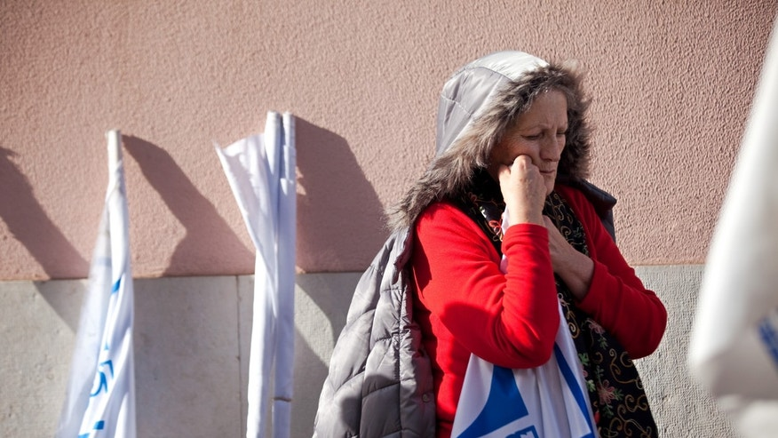 In this photo taken Jan. 30 2014, a protestor leans on a flag during a demonstration by retired teachers in Lisbon against cuts to their pensions. The Portuguese standard of living is going backwards, GDP per capita in 2010 was 80.4 percent of the EU average, In 2013 it was down to 76 percent. The Portuguese are less than three months away from their big day _ May 17 _ when they expect to get their financial sovereignty back after three years of being told what to do by foreign bailout creditors. In return for the 78 billion-euro ($107 billion) rescue that has since 2011 prevented national bankruptcy, Portugal consented to an economic crash diet: deep cuts in pay and pensions and welfare rights, steep tax increases, and an end to long-standing labor entitlements. (AP Photo/Armando Franca)