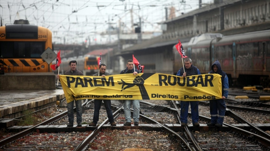 "In this photo taken Feb. 4, 2014, Portuguese railway workers hold a banner that reads in Portuguese: ""Stop Robbing. Work. Salaries. Rights. Pensions"", as they block the rail track during a protest at Lisbon's Santa Apolonia train station. The Portuguese are less than three months away from their big day _ May 17 _ when they expect to get their financial sovereignty back after three years of being told what to do by foreign bailout creditors. In return for the 78 billion-euro ($107 billion) rescue that has since 2011 prevented national bankruptcy, Portugal consented to an economic crash diet: deep cuts in pay and pensions and welfare rights, steep tax increases, and an end to long-standing labor entitlements. (AP Photo/Francisco Seco)"