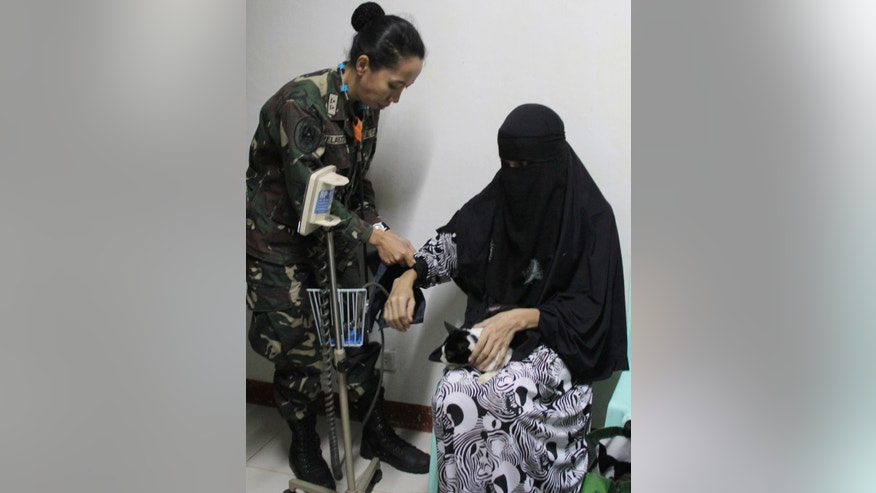 In this photo released by Armed Forces of the Philippines Western Mindanao Command, Filipino independent filmmaker Linda Bansil undergoes a medical check-up prior to a news at the Western Mindanao Command in Zamboanga city, southern Philippines, Friday, Feb. 21, 2014. Linda and her sister Nadioua were kidnapped by Muslim extremists eight months ago and escaped from their captors Thursday evening in the jungles of the southern Philippines and told authorities they were kept in isolation in a hut on a meager diet. (AP Photo/Armed Forces of the Philippines Western Mindanao Command)