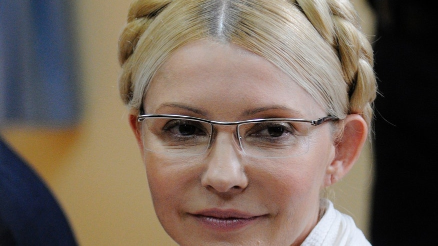 FILE - In this Monday July 11, 2011 file photo former Ukrainian Prime Minister Yulia Tymoshenko during a trial hearing at the Pecherskiy District Court in Kiev. In a fast-moving day that aimed to reshape Ukraine's political destiny, opposition leaders reached a deal Friday with the country's beleaguered president to form a new government and hold an early election, while parliament slashed his powers and voted to free his rival, former Prime Minister Yulia Tymoshenko, from prison. Legislators voted to decriminalize the count under which she was imprisoned, meaning that she is no longer guilty of a criminal offense.  The charismatic blond-braided heroine of the 2004 Orange Revolution — which also drove Yanukovych from the presidency — Tymoshenko served as prime minister and narrowly lost the 2010 presidential election to Yanukovych. The next year, she was arrested and sentenced to seven years in prison on abuse of office - charges the West has denounced as a political vendetta.  It's not immediately clear when Tymoshenko might be released from prison in the eastern city of Kharkiv. (AP Photo/Sergei Chuzavkov, File)