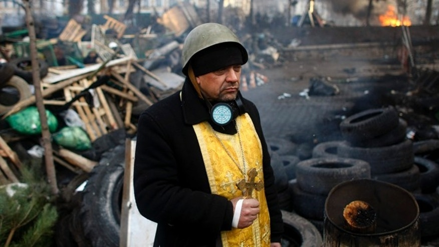 Friday, Feb. 21, 2014: A priest stands on the barricades at Independence Square in Kiev, Ukraine. The presidency said Friday that it has negotiated a deal intended to end battles between police and protesters that have killed scores and injured hundreds, but European mediators involved in the talks wouldn't confirm a breakthrough.
