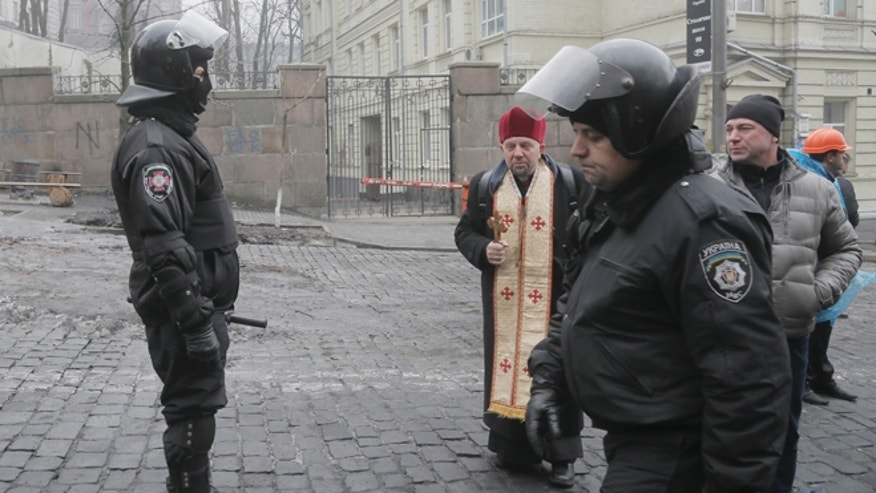 Thursday, Feb. 20, 2014: A priest and protesters talk to police officers near the Cabinet of Ministers in the center of Kiev, Ukraine. Fierce clashes between police and protesters, some including gunfire, shattered a brief truce in Ukraine's besieged capital Thursday, killing numerous people. The deaths came in a new eruption of violence just hours after the country's embattled president and the opposition leaders demanding his resignation called for a truce and negotiations to try to resolve Ukraine's political crisis.