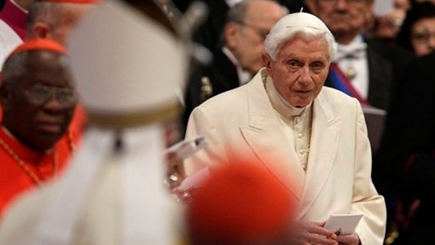 Feb.22, 2014: Pope Emeritus Benedict XVI looks at Pope Francis, left with back to camera, arriving as he attends a consistory inside the St. Peter's Basilica at the Vatican.