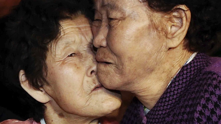 South Korean Lee Chun Hwa, right, gets a kiss from her North Korean sister Lee Chun Son before returning home after a separated family reunion meeting at the Diamond Mountain resort in North Korea, Saturday, Feb. 22, 2014. Elderly North and South Koreans separated for six decades were tearfully reuniting, grateful to embrace children, brothers, sisters and spouses they had thought they might never see again. (AP Photo/Yonhap, Lee Ji-eun) KOREA OUT