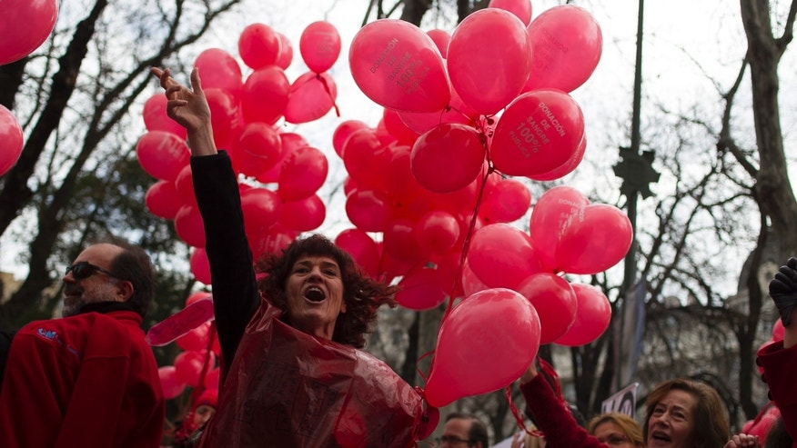 A protestor shouts slogans as she carries red balloons during a demonstration against the Madrid's regional government plans to privatize the blood donation centers, in Madrid, Spain, Sunday, Feb. 16, 2014. (AP Photo/Gabriel Pecot)
