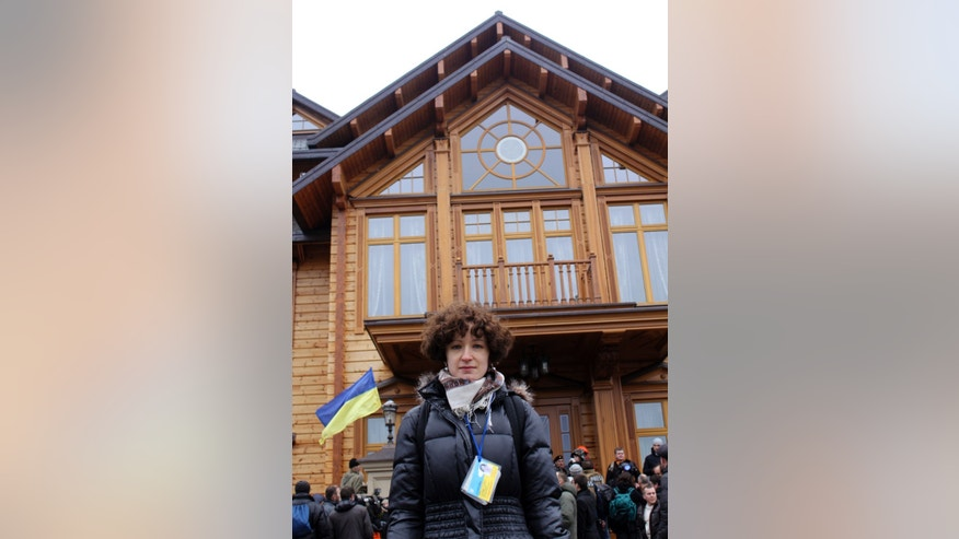 AP newswoman Maria Danilova poses for a photo in front of the Ukrainian President Yanukovych's countryside residence in Mezhyhirya, Kiev's region, Ukraine, Saturday, Feb, 22, 2014. For years, Maria has covered Ukraine's President Viktor Yanukovych, a post-Soviet strongman, whose closely guarded suburban residence of Mezhygirya became a symbol of his alleged corruption and contempt for democracy.(AP Photo)