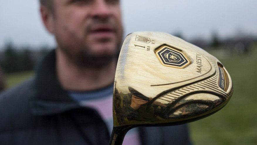 A man holds a golf club with the name of Ukrainian President Viktor Yanukovich on a golf course at the Ukrainian President Yanukovych's countryside residence in Mezhyhirya, Kiev's region, Ukraine, Saturday, Feb, 22, 2014. Viktor Yanukovych is not in his official residence of Mezhyhirya, which is about 20 kilometres north of the capital. Ukrainian security and volunteers from among Independence Square protesters have joined forces to protect the presidential countryside retreat from vandalism and looting.(AP Photo/Andrew Lubimov)
