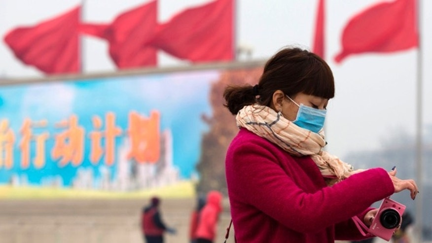 "Feb. 13, 2014: A woman wears a mask as she walks past the words ""Action Plan"" displayed on a screen on Tiananmen Square during a hazy day in Beijing."