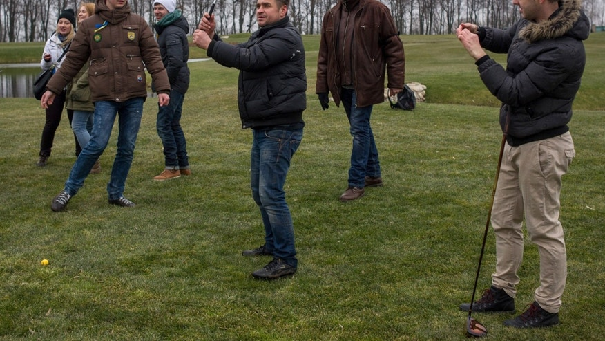 Feb, 22, 2014: Protesters try to play on a golf course at former Ukrainian President Yanukovych's countryside residence in Mezhyhirya, Kiev's region, Ukraine.