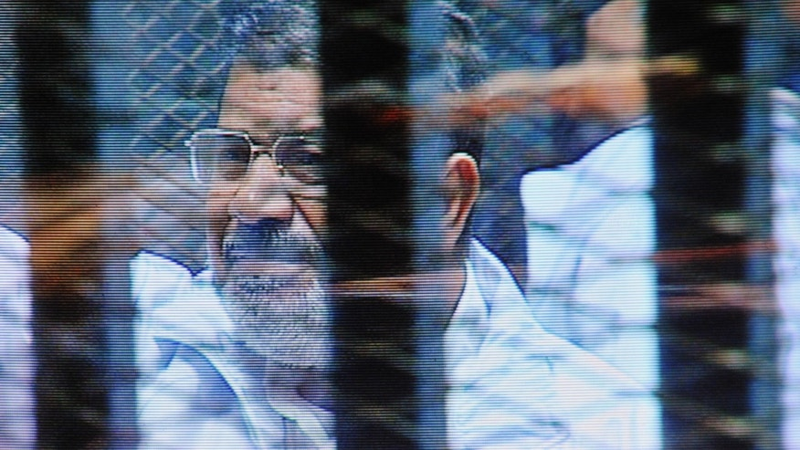 FILE - In this  Sunday, Feb. 16, 2014 file photo, Egypt's ousted President Mohammed Morsi in a soundproof barred glass cage is seen on a monitor set up outside a courtroom where Morsi and 35 others are facing charges of conspiring with foreign groups and undermining national security, in Cairo, Egypt. Morsi, toppled in July by the military, faces a host of criminal charges and appeared in court Saturday, Feb. 22, 2014, in a case that charges him and 130 others over prison breaks that freed some 20,000 inmates during the 18-day revolt in 2011 that toppled autocrat Hosni Mubarak. Morsi himself was freed in a prison break before becoming the nation's first freely elected president. (AP Photo/Mohammed al-Law, File)