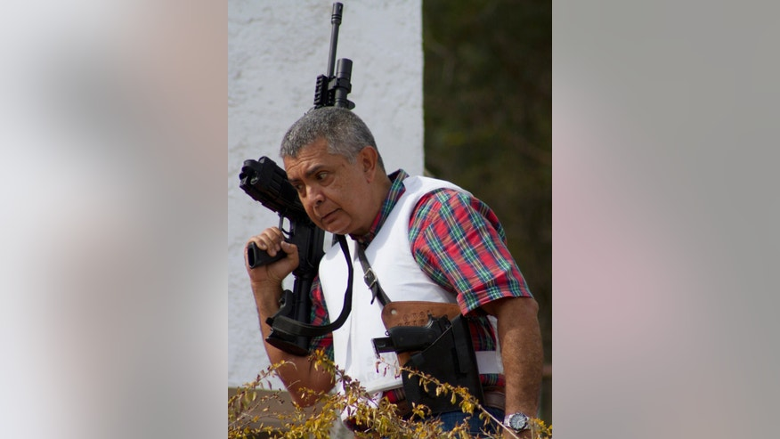 "Retired Venezuelan Army Gen. Angel Vivas, armed and wearing a flak jacket, walks around his home in Caracas, Venezuela, Sunday, Feb. 23, 2014. President Nicolas Maduro ordered on Saturday the arrest and investigation of the retired general for his statements on YouTube and Twitter. Maduro said Vivas is instigating violence at a time when two weeks of anti-government protests have left 10 dead and over 100 wounded. Vivas became an opponent of the Venezuelan government since his 2007 resignation as director of the Ministry of Defense Engineering for his opposition to the military's adoption of the slogan ""Fatherland, socialism or death, we shall overcome"", created in Cuba. (AP Photo/Juan Manuel Hernandez)"