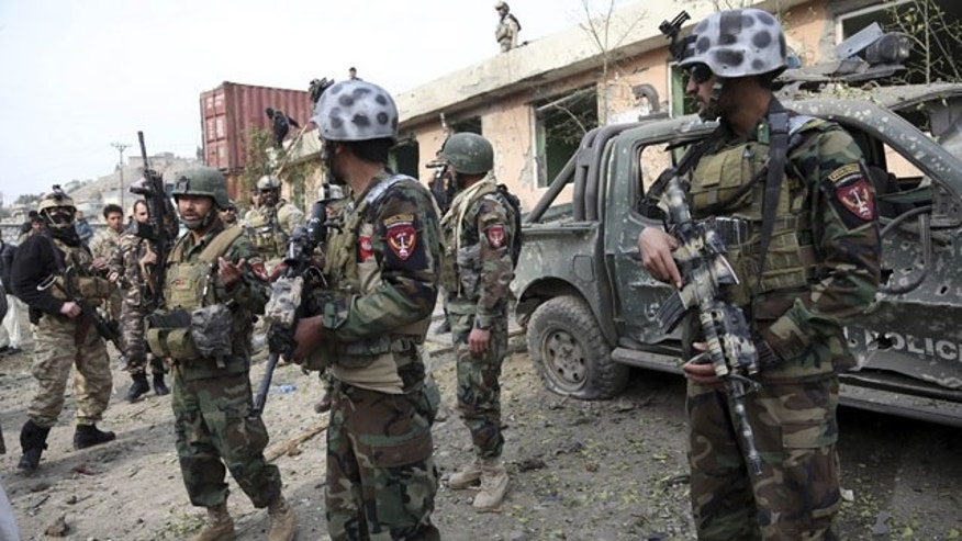 February 21, 2014: Afghan security forces personnel arrive at the site of a suicide bombing at a police compound in Surobi district of Kabul, Afghanistan.  (AP Photo/Rahmat Gul)