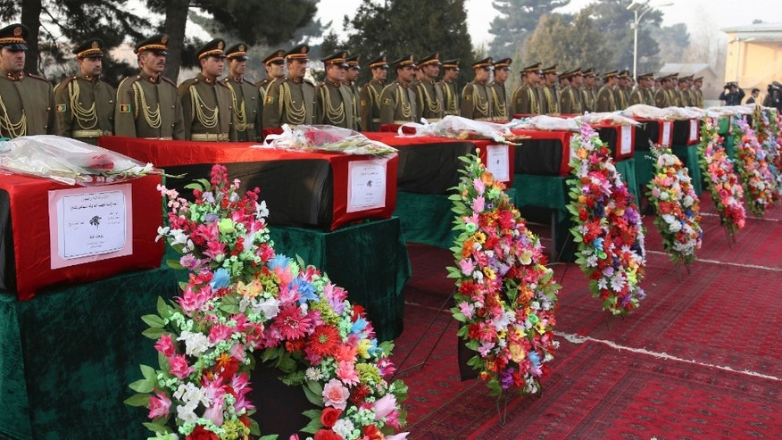 Members of the Honor Guard stand at attention near the caskets of victims of Afghan national army soldiers during a funeral ceremony in Kabul, Afghanistan, Monday, Feb. 24, 2014. Hundreds of heavily armed Taliban insurgents attacked the checkpoint on Sunday, officials said, killing 21 soldiers in the deadliest single incident for the Afghan army in at least a year. (AP Photo/Rahmat Gul)