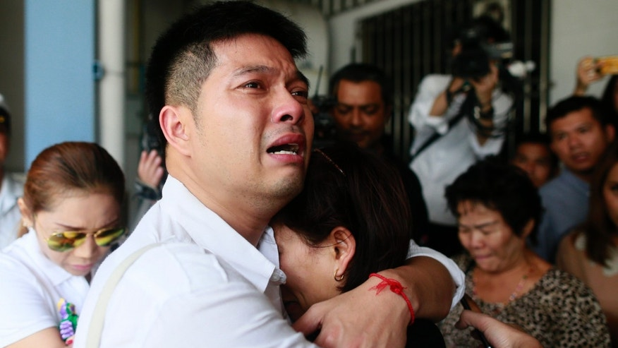 Tayakorn Yos-ubon, left, and Noppawan Chairat, right, the parents of two children killed in Sunday's bomb attack on an anti-government protest site, embrace each other as they wait for their children's bodies at a hospital in Bangkok Monday, Feb. 24, 2014. Two young siblings, 6-year-old girl Patcharakorn and her 4-year-old brother Korawit, along with another woman were killed in an apparent grenade attack against anti-government protesters occupying an upscale shopping area of Thailand's capital on Sunday, the latest violence in a months-long political crisis that is growing bloodier by the day. (AP Photo/Wason Wanichakorn)