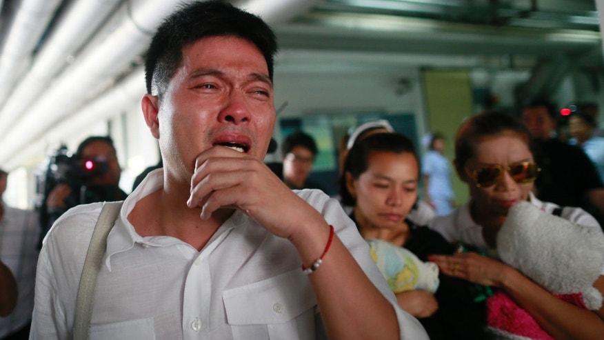 Tayakorn Yos-ubon, left, and Noppawan Chairat, center, the parents of two children killed in Sunday's bomb attack on an anti-government protest site, react as they wait for the bodies at a hospital in Bangkok, Thailand, Monday, Feb. 24, 2014. Two young siblings, 6-year-old girl Patcharakorn and her 4-year-old brother Korawit, along with another woman were killed in an apparent grenade attack against anti-government protesters occupying an upscale shopping area of Thailand's capital on Sunday, the latest violence in a months-long political crisis that is growing bloodier by the day. (AP Photo/Wason Wanichakorn)
