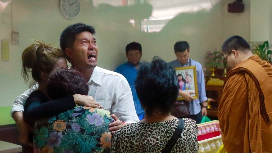 Tayakorn Yos-ubon, the father of two children killed in Sunday's bomb attack on an anti-government protest site, is embraced by his family as he breaks down during a ceremony at a hospital when he collects their bodies, Monday, Feb. 24, 2014, in Bangkok, Thailand. Two young siblings, 6-year-old girl Patcharakorn and her 4-year-old brother Korawit, along with another woman were killed in an apparent grenade attack against anti-government protesters occupying an upscale shopping area of Thailand's capital on Sunday, the latest violence in a months-long political crisis that is growing bloodier by the day. (AP Photo/Wason Wanichakorn)