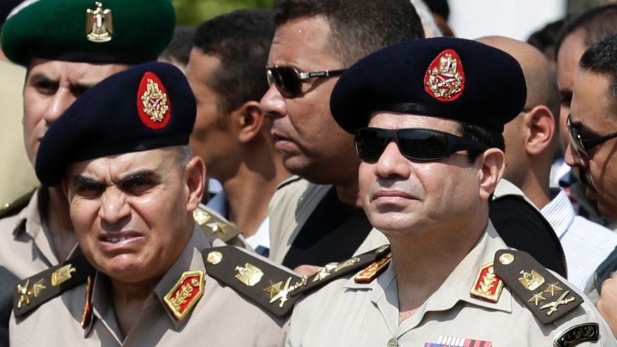 Sept. 20, 2013 - FILE photo of Egypt's Defense Minister Gen. Abdel-Fattah el-Sissi, center, Egyptian Prime Minister Hazem el-Beblawi, right, and army's Chief of Staff Lt. Gen. Sedki Sobhi, left, at the funeral of Giza Police Gen. Nabil Farrag in Cairo, Egypt. The head of Egypt's military, Abdel-Fattah el-Sissi, is riding on a wave of popular fervor that is almost certain to carry him to election as president.