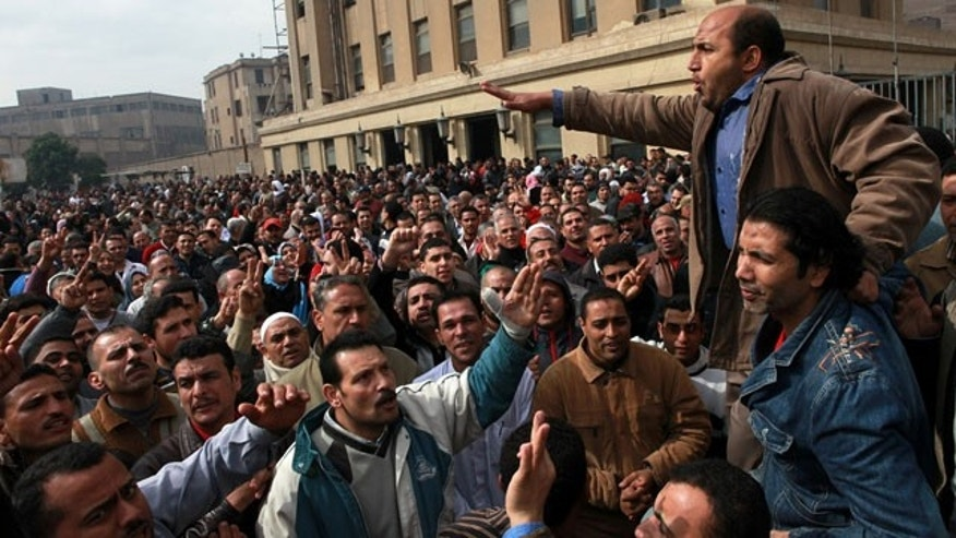 February 15, 2014: Textile workers strike to demand a minimum wage, the removal of their company's head and the head of the firm's holding company, and back pay of yearly bonuses in Mahalla al-Kobra, Egypt. (AP Photo/Sabry Khaled, El Shorouk Newspaper)
