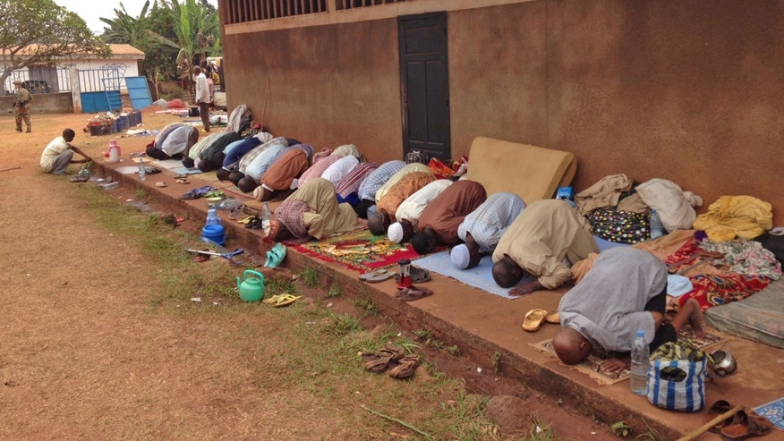 In this photo taken on Sunday, Feb. 23, 2014, Muslims pray as they hide at a Catholic church in Carnot a town 200 kilometers (125 miles) from the Cameroonian border, in, Central African Republic. The Christian militiamen knew hundreds of Muslims were hiding at the Catholic church and came with their ultimatum: Evict the families to face certain death or else the entire place would be burned to the ground.  (AP Photo/Krista Larson)