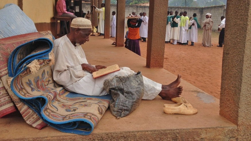 In this photo taken on Sunday, Feb. 23, 2014, A Muslim man reads religions script at a Catholic church in Carnot a town 200 kilometers (125 miles) from the Cameroonian border, in, Central African Republic. The Christian militiamen knew hundreds of Muslims were hiding at the Catholic church and came with their ultimatum: Evict the families to face certain death or else the entire place would be burned to the ground.  (AP Photo/Steve Niko)