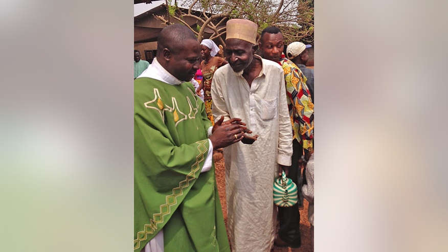 In this photo taken on Sunday, Feb. 23, 2014, Father Justin Nary, left, greets Ousmane Mahamat, one of the 800 Muslims seeking refuge in a Catholic church in Carnot a town 200 kilometers (125 miles) from the Cameroonian border, in, Central African Republic. The Christian militiamen knew hundreds of Muslims were hiding at the Catholic church and came with their ultimatum: Evict the families to face certain death or else the entire place would be burned to the ground.  (AP Photo/Krista Larson)