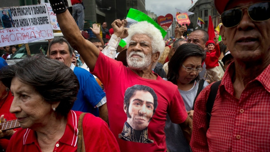 In this Sunday, Feb. 23, 2014 photo, a man wearing a T-shirt of Venezuela's independence hero Simon Bolivar chants pro-government slogans during a march by elderly people in Caracas, Venezuela. The march, organized by the government in the name of peace, ended at Miraflores presidential palace where the seniors met with President Nicolas Maduro. (AP Photo/Rodrigo Abd)