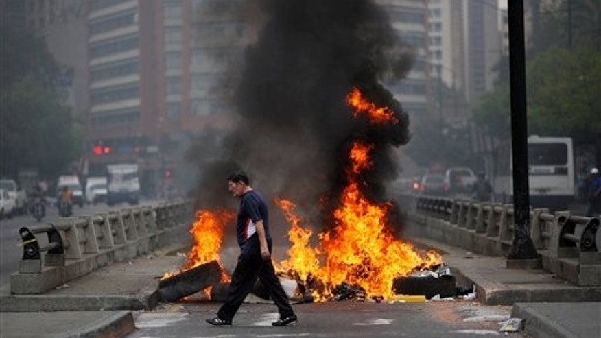 A pedestrian walks in front of a burning barricade blocking the highway in Chacao, Caracas, Venezuela, Monday, Feb. 24, 2014. Traffic has come to a halt in parts of the Venezuelan capital because of barricades set up by opposition protesters across major thoroughfares. The protests are part of a wave of anti-government demonstrations that have swept Venezuela since Feb. 12 and have resulted in at least 10 deaths. The protests in the capital Monday were peaceful. Police and National Guard troops stood by but did not act to remove the barricades despite the effect on the morning commute. (AP Photo/Rodrigo Abd)