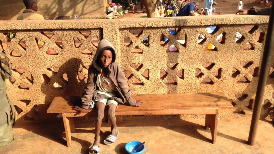 Ibrahim Adamou sits on a bench at a Catholic church in Carnot a town 200 kilometers (125 miles) from the Cameroonian border, in the Central African Republic Monday, Feb. 24, 2014. Ibrahim Adamou wasn't sure whether any of his five siblings had survived the attack by Christian militiamen who opened fire on his family as the group of herders journeyed on foot. His parents already had been killed in front of him. (AP Photo/Krista Larson)