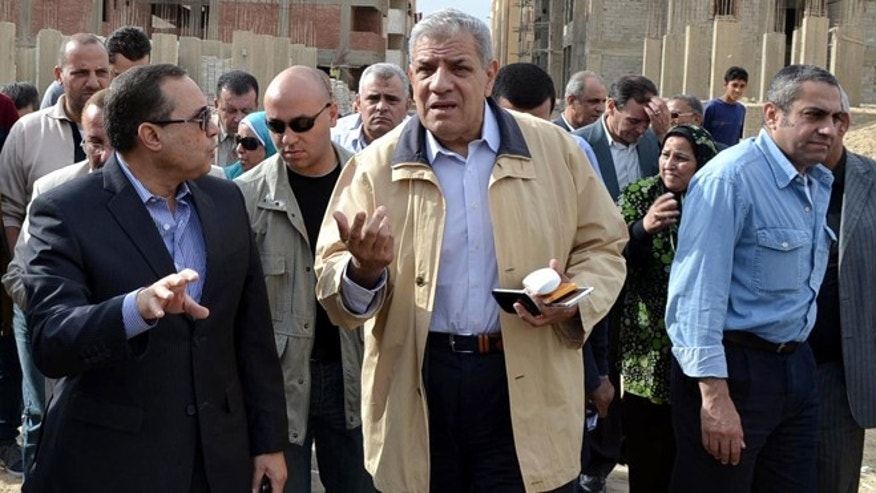 Nov. 24, 2013: In this photo, Ibrahim Mehlib, center, tours a government housing project in Ismailiya, Egypt.