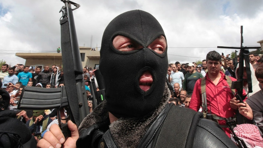 FILE -- In this May 21, 2012, file photo, a masked Lebanese Sunni gunman holds up his weapon as he attends the funeral procession of anti-Syrian regime Sunni cleric Sheik Ahmed Abdul-Wahid, who was shot at a Lebanese army checkpoint, at his hometown village of Beireh, in Akkar, north Lebanon. From radical preachers to irreverent taxi drivers, anger is spreading through Lebanon's Sunni community toward the country's military, adding a dangerous twist to Lebanon's instability, already shaken by relentless bombings. Many Sunnis accuse the military of siding with their rivals, the powerful Shiite group Hezbollah, as sectarian tensions grow in Lebanon, stoked by the civil war in neighboring Syria. (AP Photo/Hussein Malla, File)