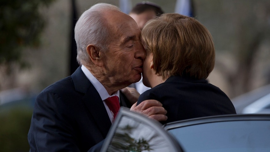 Israel's President Shimon Peres kisses German Chancellor Angela Merkel as she arrives to receive the Presidential Medal ceremony at the President's residence in Jerusalem,Tuesday, Feb. 25, 2014. The Presidential Medal is the highest civil medal given by the State of Israel. (AP Photo/Ariel Schalit2