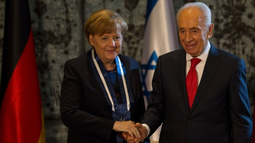 Israel's President Shimon Peres and German Chancellor Angela Merkel, left, after she received the Presidential Medal of Distinction during a ceremony at the President's residence in Jerusalem,Tuesday, Feb. 25, 2014.The Presidential Medal is the highest civil medal given by the State of Israel. (AP Photo/Ariel Schalit)